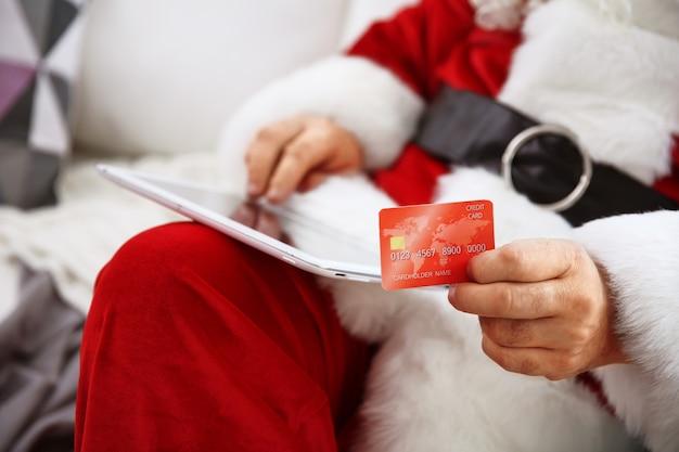 自宅のソファにクレジットカードとタブレットを持つサンタクロース