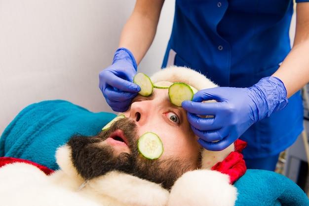 キュウリの顔のマスクとサンタクロース。美容スパでサンタクロースの服のクリスマス男。