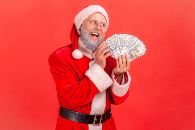 Santa claus with excited expression, greedy male with fan of dollars, looking at banknotes.
