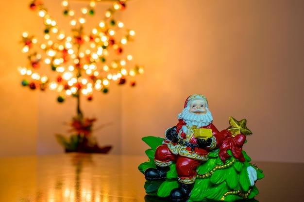 배경에 선물과 흐릿한 크리스마스 트리가 있는 산타클로스