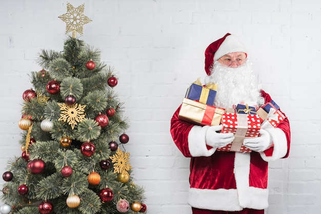 Santa claus with gifts in hands near christmas tree