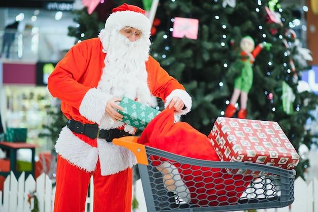 Дед мороз с подарками в тележке для покупок в торговом центре.