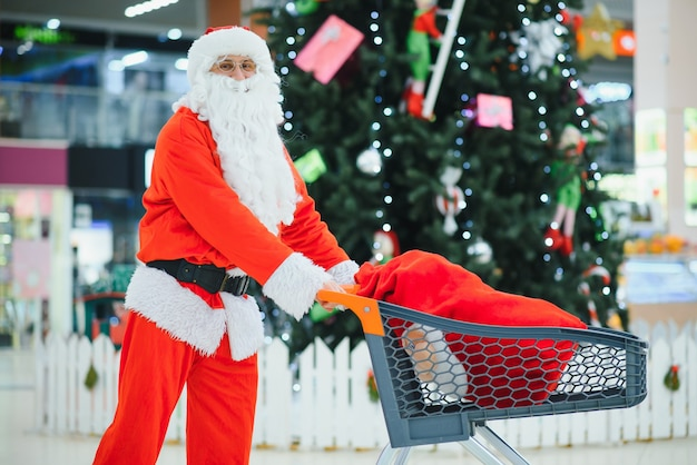 Дед мороз с подарками в торговом центре на фоне елки