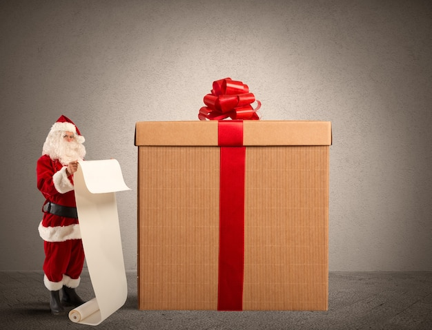 ギフトリストと大きなプレゼントボックス付きのサンタクロース