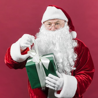 Santa claus with green gift box in hands