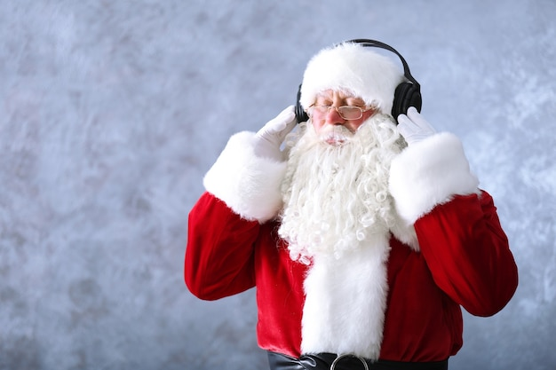 Santa claus with headphones listening to music on gray wall background