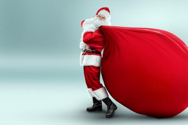 大きな赤い贈り物の袋を持ったサンタクロース