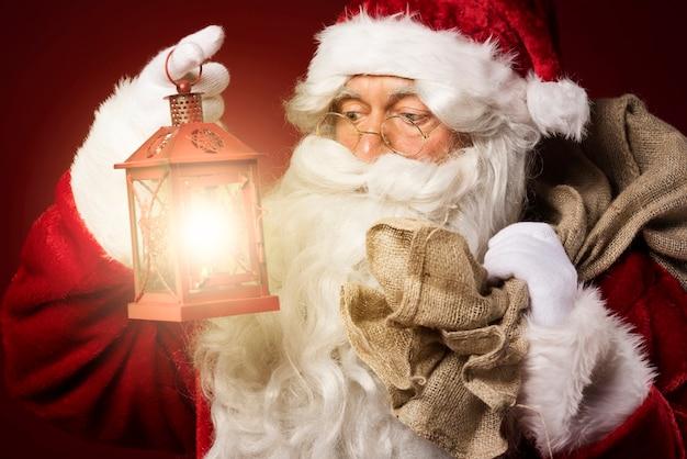 Babbo natale con una lanterna e un sacco di regali