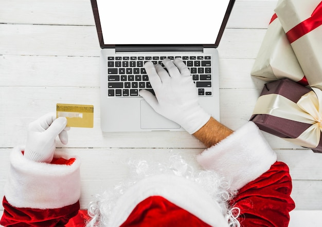 Santa claus with laptop and credit card at table