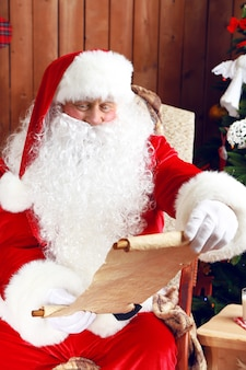 Санта-клаус со списком подарков, сидя в удобном кресле-качалке возле рождества у себя дома