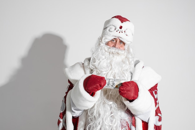 Santa claus with long white beard shows money, picture isolated on white wall
