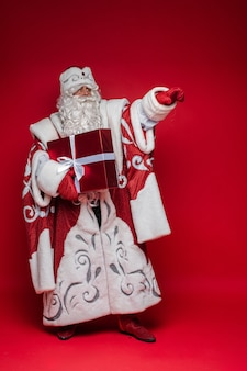 Santa claus with long white beard shows something with his hand and holds a gift, picture isolated on red wall