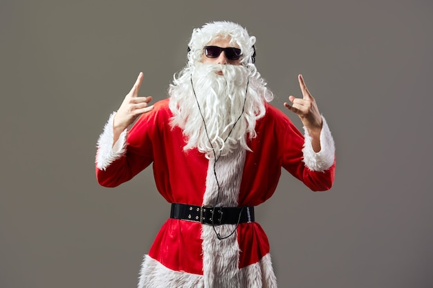 Santa claus with a long white beard in sunglasses and headphones listen the rock music