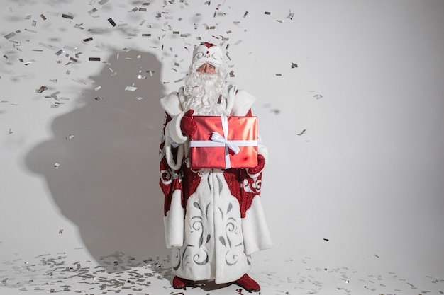 Santa claus with long white beard with big red box with a christmas present in his hands, picture isolated on white wall