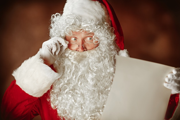 Santa claus with a luxurious white beard, santa's hat and a red costume reading letter