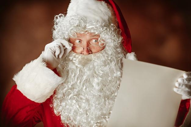 Babbo natale con una lussuosa barba bianca, cappello di babbo natale e una lettera di lettura in costume rosso