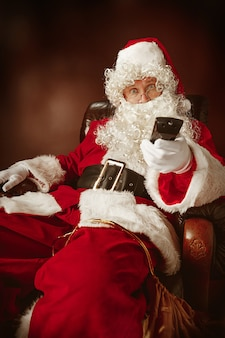 Santa claus with a luxurious white beard, santa's hat and a red costume sitting in a chair with tv remote control