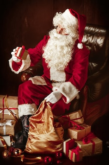 Santa claus with a luxurious white beard, santa's hat and a red costume sitting with gifts