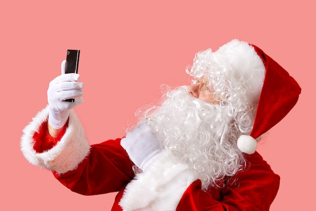 Santa claus with mobile phone isolated on pink background