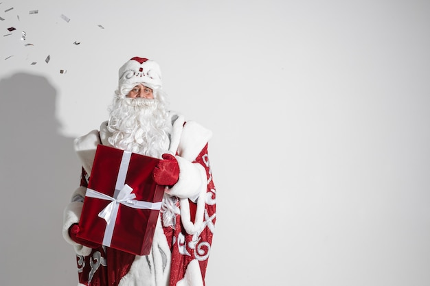 Santa claus with red xmas gift posing in studio