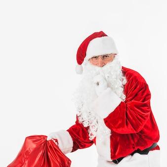 Santa claus with sack showing secret gesture