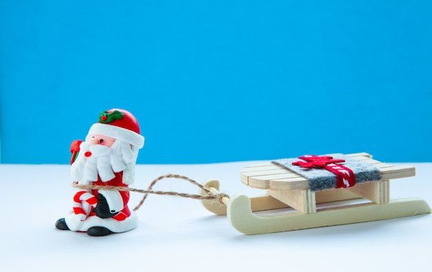 Santa claus with sleigh on a light blue background, christmas mood, new year holidays concept