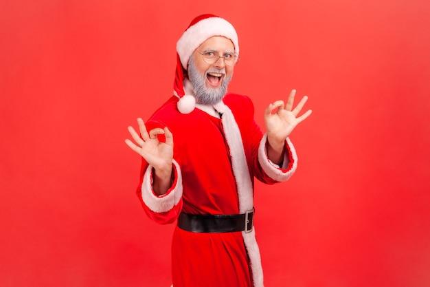 확인 제스처를 만드는 미소와 함께 산타 클로스는 기분 좋은 표시를 보여줍니다.