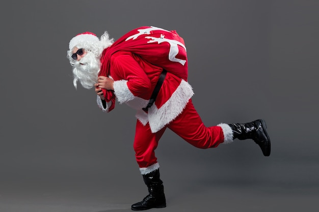 Santa claus with sunglasses runs with the bag in christmas gifts on his back on the white background. .