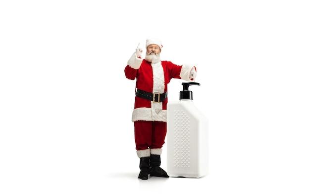 分離されたクリスマスプレゼントのようなcovidに対する巨大な防腐剤を持つサンタクロース