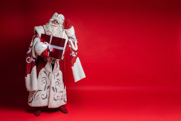 Santa claus with xmas gift puts his hand to head, tryes to listen
