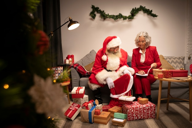 Santa claus and woman setting up christmas gifts