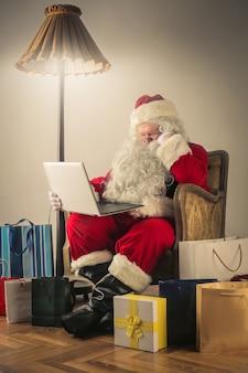 그의 노트북에서 일하는 산타 클로스