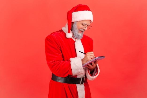 산타클로스는 공책에 글을 쓰고 크리스마스 휴가를 위한 위시리스트를 만듭니다.