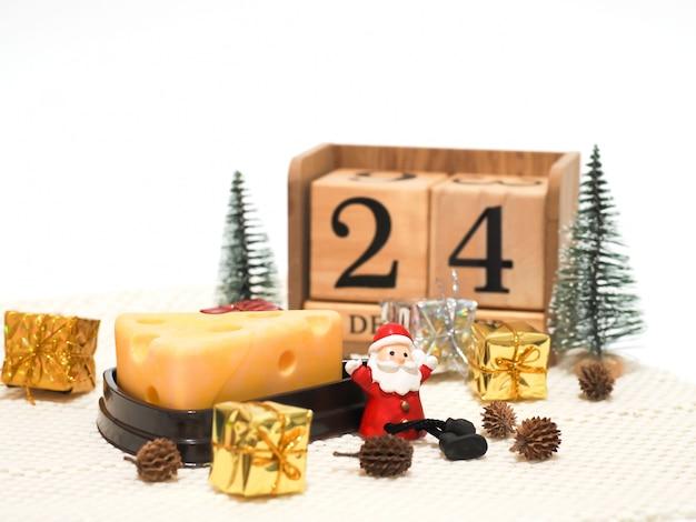 サンタクロースがクリスマスケーキを待っているチーズケーキで座っています。