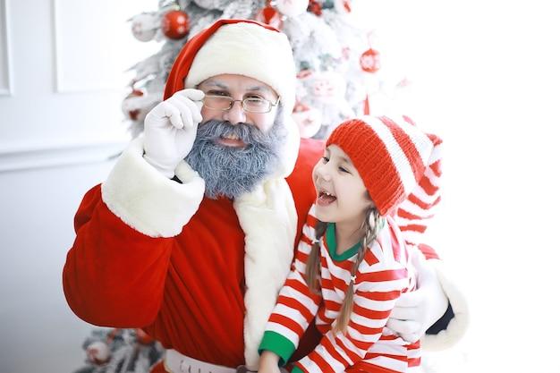 サンタクロースヘルパークリスマスエルフの衣装を着たかわいい子供たちサンタクロースからの贈り物