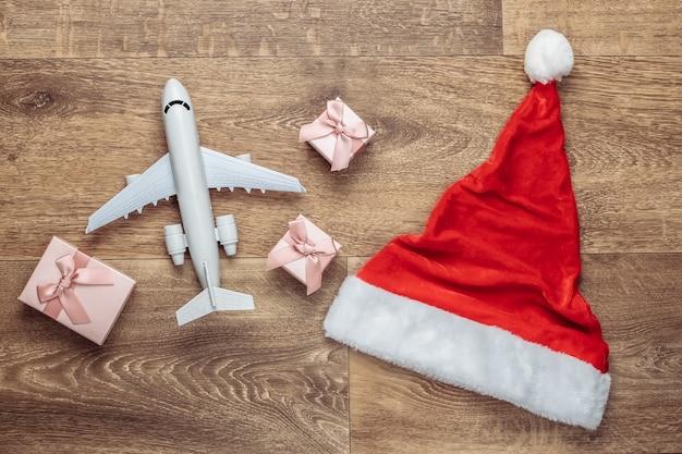 Доставка санты. шляпа санты, подарочные коробки, самолет на полу. плоская композиция.