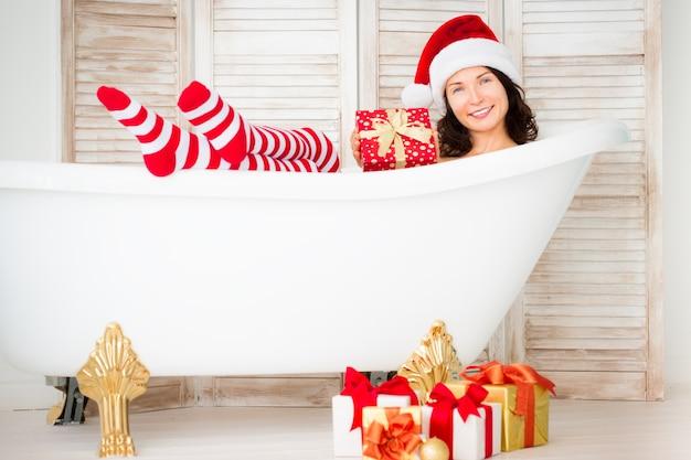 家で楽しんでいるサンタの女の子。クリスマス休暇のコンセプト