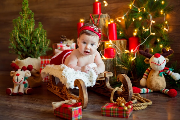 Santa girl lies on a wooden sleigh with gifts surrounded by a christmas tree with garlands and toys
