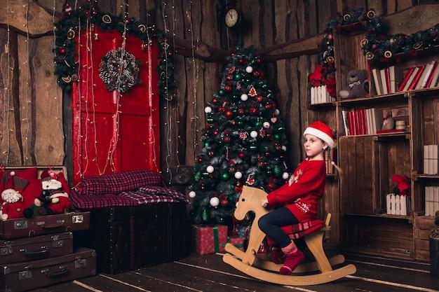 Santa girl riding rocking horse on background of christmas decorations.