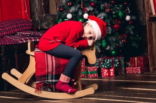 クリスマスの装飾の背景にロッキングホースに乗ってサンタの女の子。