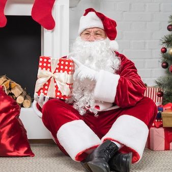 Santa in glasses sitting with gift boxes on floor