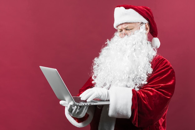 Santa in glasses typing on laptop