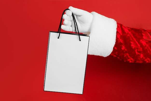 빨간색에 흰색 쇼핑백과 산타 손