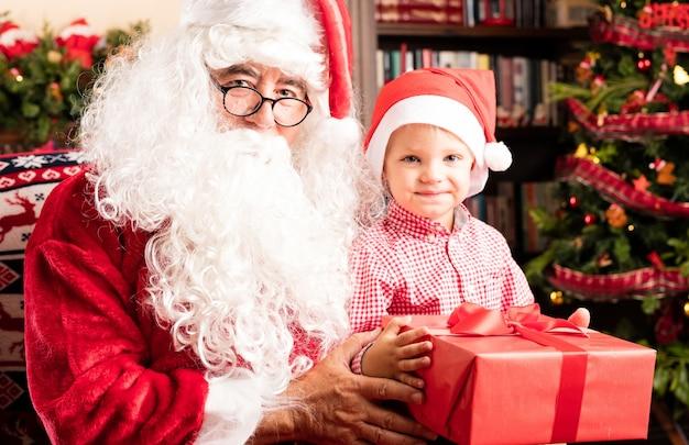 Di santa consegnare un regalo rosso ad un bambino