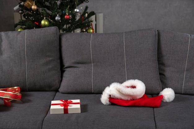 산타 모자와 회색 소파에 선물 상자를 엽니다. 섣달 그믐 끝