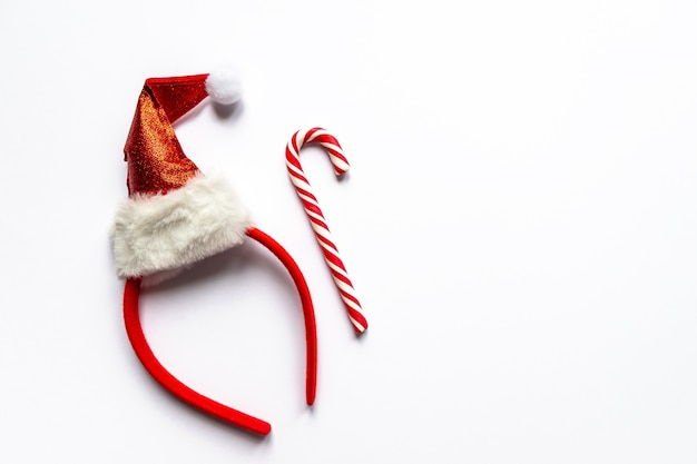Santa hat and candy cane on white background creative new year flat lay with copy space minimalistic...