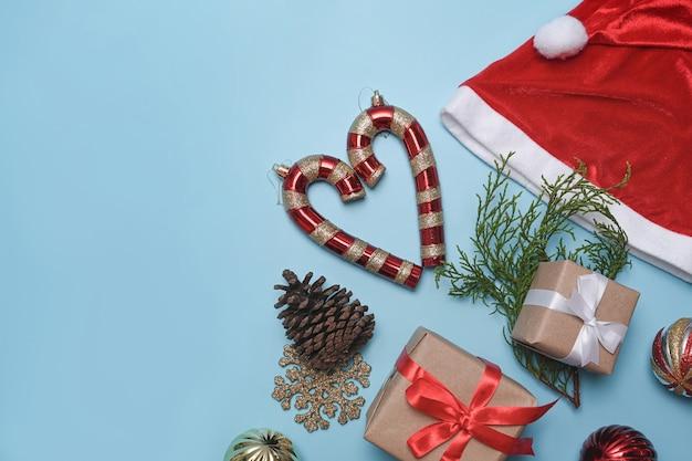 파란색 배경에 산타 모자, 크리스마스 선물, 솔방울과 전나무 나뭇가지.