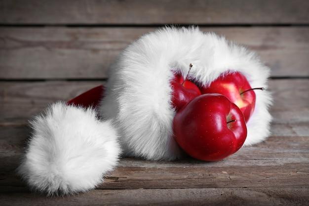 木製の背景にリンゴでいっぱいのサンタの帽子、クローズアップ