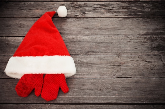 Santa hat and red mitten on old wooden background