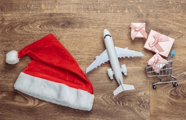 Шапка санты, тележка для покупок с подарочными коробками, самолет на полу. плоская композиция.